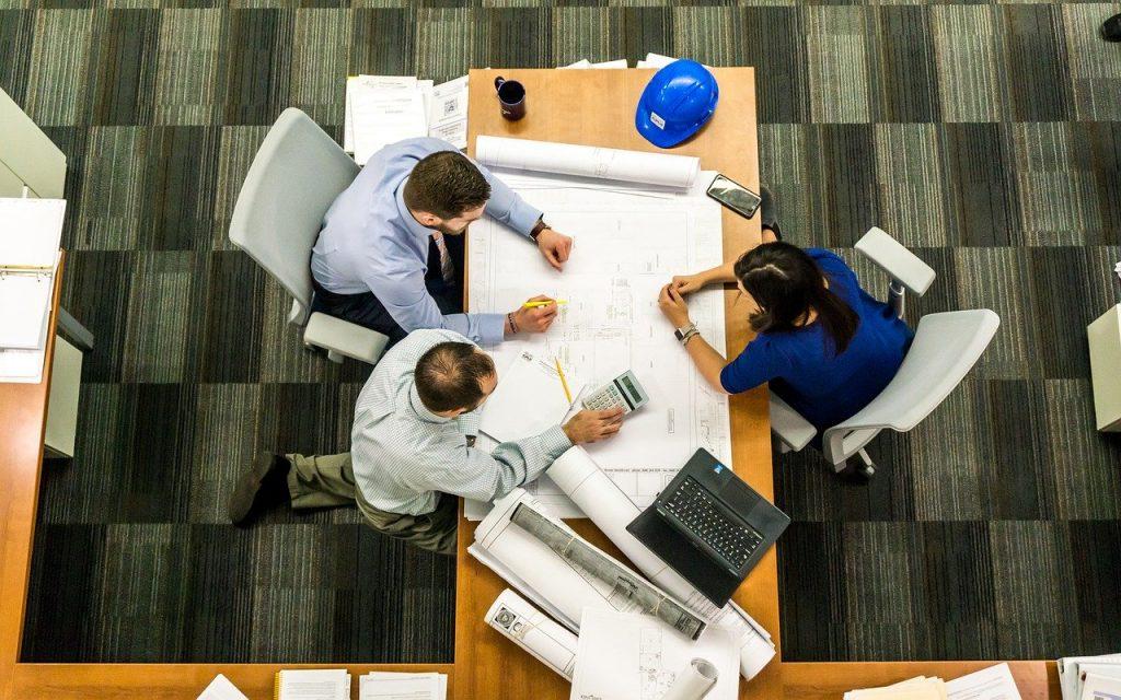 trois personnes assises autour du même bureau lors d'une réunion